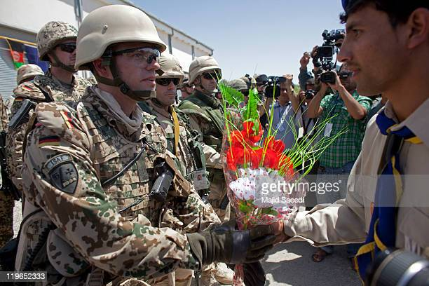 German soldiers of NATO's International Security Assistance Force receive plastic flowers during a security transition ceremony July 23, 2011 in...
