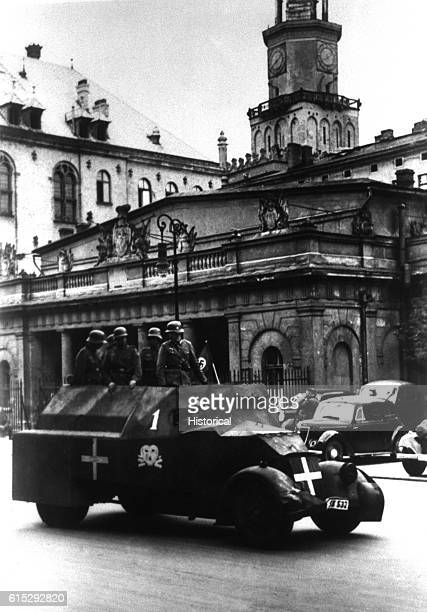 German soldiers ride through a Polish town in an armored vehicle September 1939