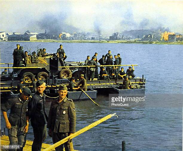 German soldiers row vehicles across an unidentified body of water towards a buring town on the far shore Soviet Union 1941 or 1942 The image was...