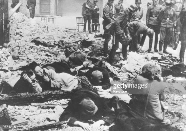 German soldiers searching the belongings of Jews rounded up in the Warsaw ghetto after the uprising, while frightened Jews await their turn.
