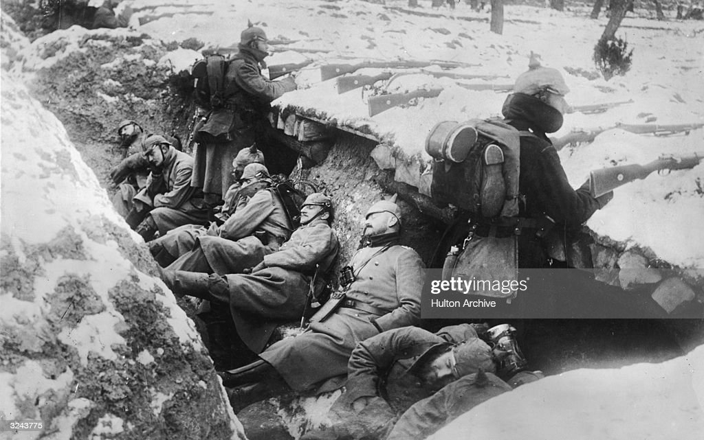 German soldiers sleeping in their trench in the snow as two stand guard with rifles poised, near the Aisne River valley, Western Front, France, World War I.