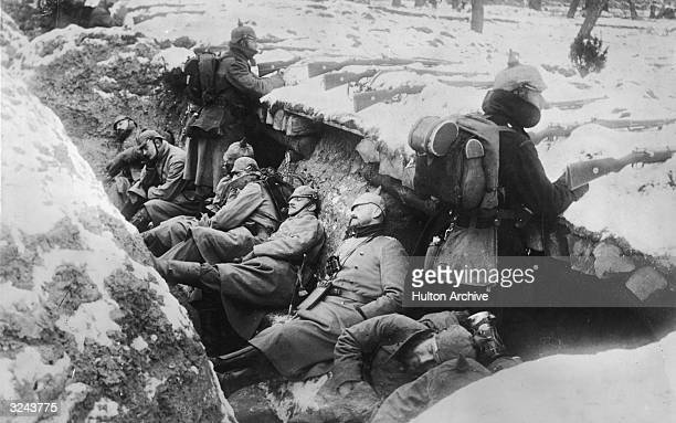 German soldiers sleeping in their trench in the snow as two stand guard with rifles poised, near the Aisne River valley, Western Front, France, World...