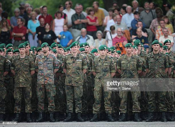 German soldiers stand in front of onlookers during the roll call of the 17th German ISAF contingent at the Regenstorplatz on June 3 2008 in Lemgo...