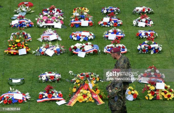 TOPSHOT German soldiers stands next to wreaths of flowers during a ceremony at the German war cemetery in La Cambe Normandy northwestern France on...