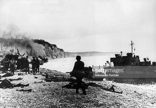 German soldiers walking along the Dieppe shore among the fallen and the wrecks of the British Expeditionary Force Dieppe 19th August 1942