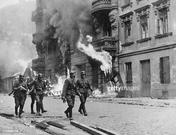 German soldiers walking by fires set in the warsaw ghetto, which was burned to the ground after the uprising, world war ll, poland, 1944.