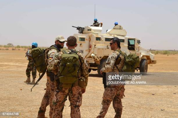 German soldiers with the United Nations Multidimensional Integrated Stabilization Mission in Mali speak next to a Nigerian armored vehicle at a...