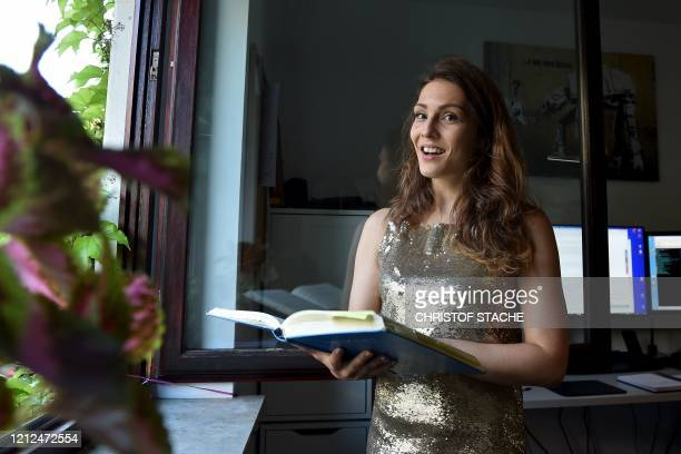 German soprano singer Nicole Tschaikin gets prepared before performing as every sunday evening from her apartment window in Munich, southern Germany,...
