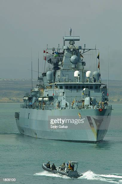 German speedboat passes the German naval frigate Mecklenburg-Vorpommern as itn embarks February 22, 2003 from the port at Djibouti Town, Djibouti....