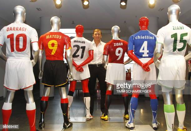 German sports equipment manufacturer Puma's CEO Jochen Zeitz poses for photographers with mannequins wearing football shirts ahead of the company's...