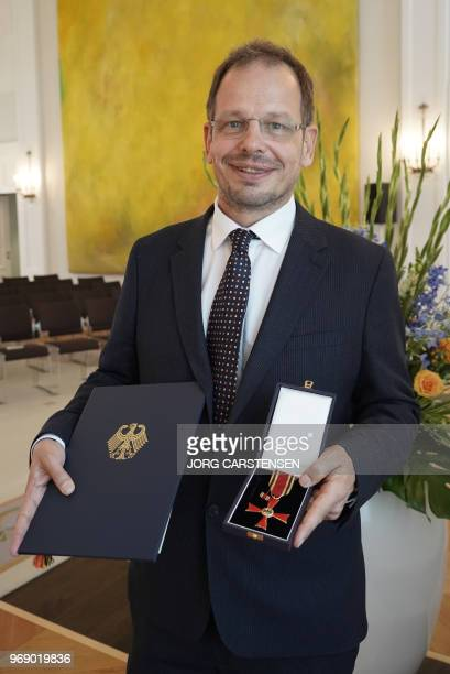 German sports journalist Hajo Seppelt presents the Federal Cross of Merit he was awarded by the German President for his outstanding commitment...