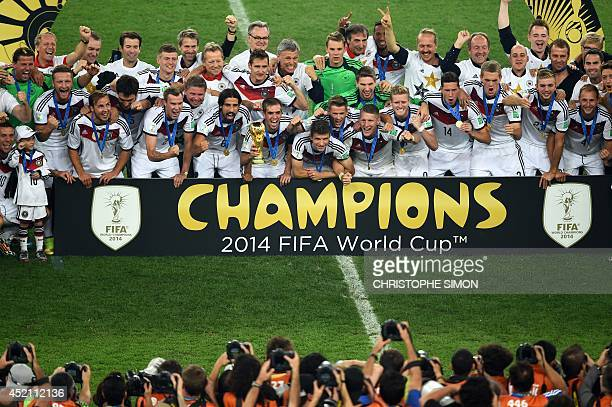 German squad members pose with the World Cup trophy after winning the 2014 FIFA World Cup final football match between Germany and Argentina at the...