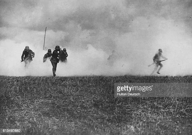 German storm troopers led by an officer emerge from a thick cloud of phosgene poison gas laid by German forces as they attack British trench lines...