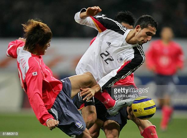 German striker Kevin Kuranyi vies against Korean Dong-Jin Kim 19 December 2004 at the Busan Asiad Main Stadium, during their friendly football match....