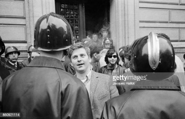 German student leader Daniel CohnBendit surrounded by police officers in front of the Sorbonne