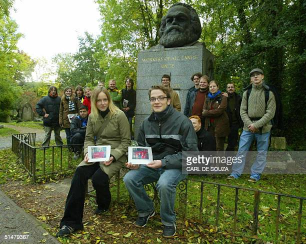 German students Katharina Dahme and Maik Hensel hold pictures taken of themselves at a German TV show by Karl Marx's grave in Highgate London 14...