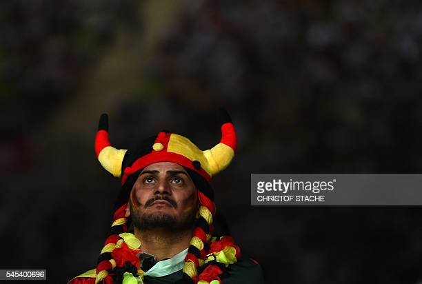 German supporter follows the Euro 2016 semifinal football match Germany v France taking place in Marseille at the Olympic stadium in Munich southern...