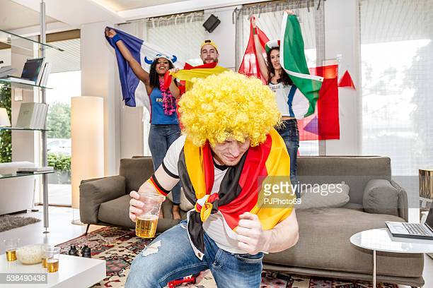 German supporter rejoices holding glass of beer