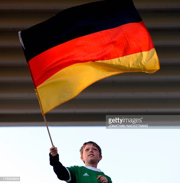 A German supporter waves his team's flag prior to the UEFA Women's European Championship Euro 2013 group B football match Germany vs Netherlands on...