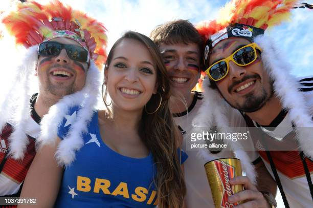 German Supporters from Heilbronn pose with a supporter of Brazil prior to the FIFA World Cup 2014 group G preliminary round match between Germany and...