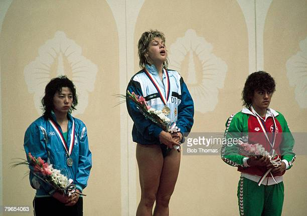 German swimmer Silke Horner of the East Germany team stands on the podium after coming first to win the gold medal in a world record time with Huang...