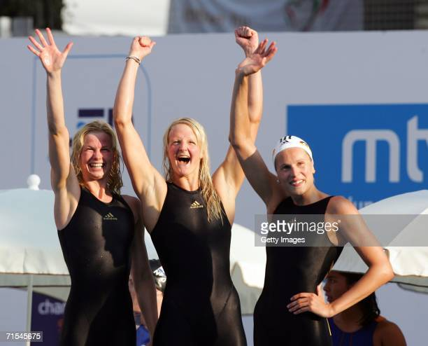 German swimmers Petra Dallmann Daniela Goetz and Britta Steffen celebrate their victory in the 400m freestyle relay with the World Record time of 3...