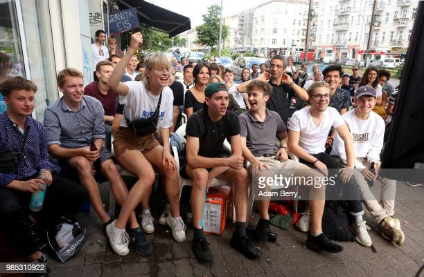 German team fans watch Germany play South Korea in the teams' World Cup match on the sidewalk outside a late night shop on June 27 2018 in Berlin...