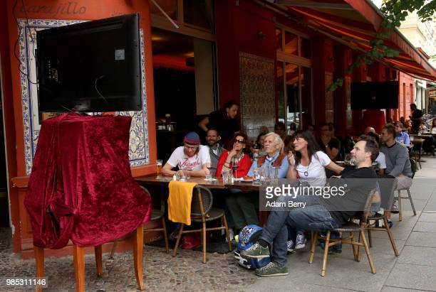 German team fans watch Germany play South Korea in the teams' World Cup match on the sidewalk outside a restaurant on June 27 2018 in Berlin Germany...