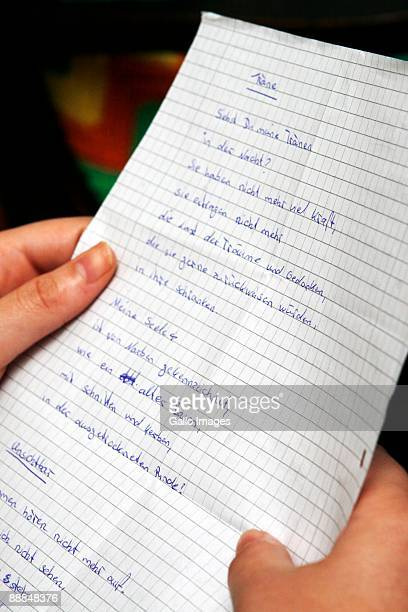 A German teenager refered by local press as Sandra holds one of the letters that she wrote detailing her horrific experience after being allegedly...