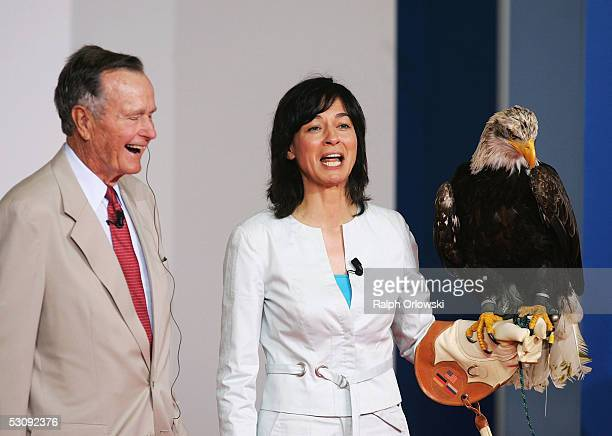 German television host Maybritt Illner stands next to former US President George Bush whilst holding an American Bald Eagle during the 'Point Alpha...