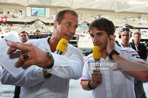 German television presenter Kai Ebel talks with Timo Glock of Germany and Toyota before the start of the Abu Dhabi Formula One Grand Prix at the Yas...