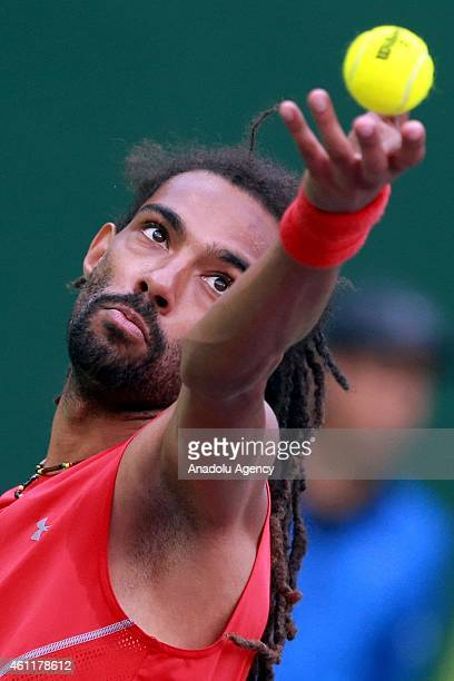 German tennis player Dustin Brown serves the ball to David Ferrer of Spain during their quarterfinal tennis match in the Qatar's ExxonMobil Open at...
