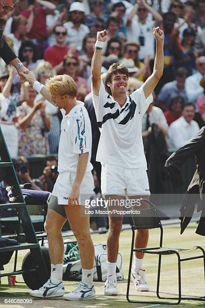 German tennis player Michael Stich raises his hands in celebration after beating fellow German player Boris Becker pictured shaking hands with the...