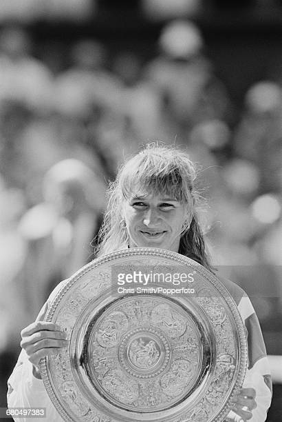 German tennis player Steffi Graf holds the Venus Rosewater Dish trophy after winning the final of the Ladies' Singles tournament against Argentine...