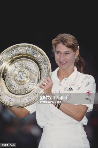 German tennis player Steffi Graf holds the Venus Rosewater Dish trophy after winning the final of the Ladies' Singles tournament against Monica Seles...