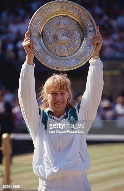 German tennis player Steffi Graf holds the Venus Rosewater Dish trophy up in the air after winning the final of the Ladies' Singles tournament...