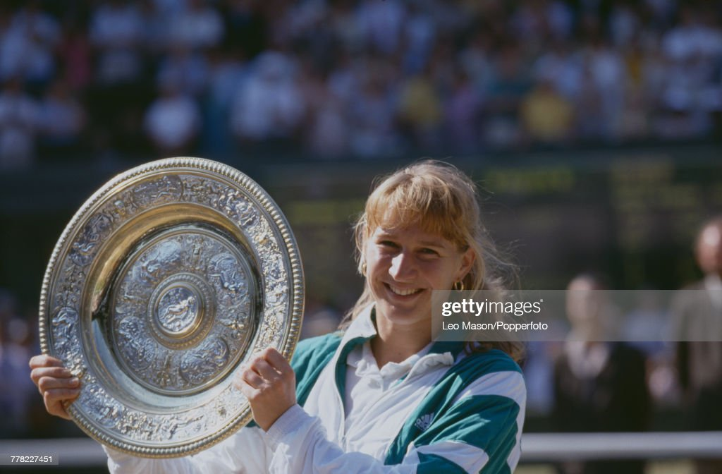 German tennis player Steffi Graf holds the Venus Rosewater Dish trophy up in the air after winning the final of the Ladies' Singles tournament against Gabriela Sabatini, 6-4, 3-6, 8-6 at the Wimbledon Lawn Tennis Championships at the All England Lawn Tennis Club in Wimbledon, London on 6th July 1991.