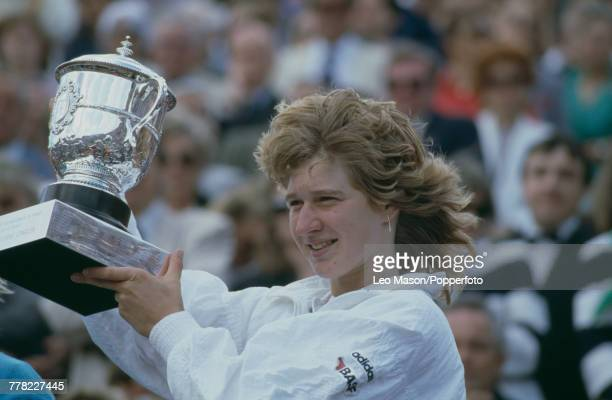 German tennis player Steffi Graf holds up the trophy after beating American tennis player Martina Navratilova 64 46 86 to win the final of the...