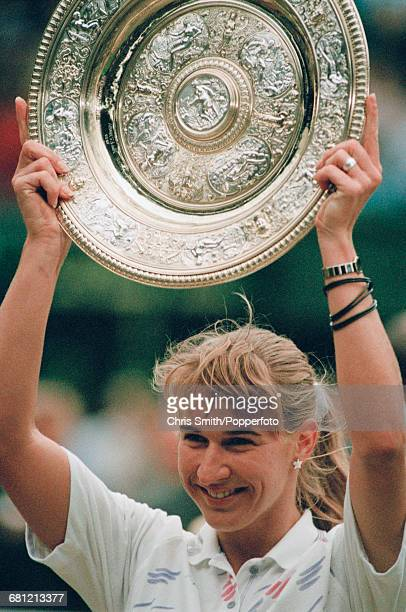 German tennis player Steffi Graf holds up the Venus Rosewater Dish trophy after winning the final of the Ladies' Singles tournament against...