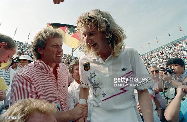German tennis player Steffi Graf is congratulated October 01 by her coach Klaus Hofsass after she beat Gabriela Sabatini of Argentina in the women's...