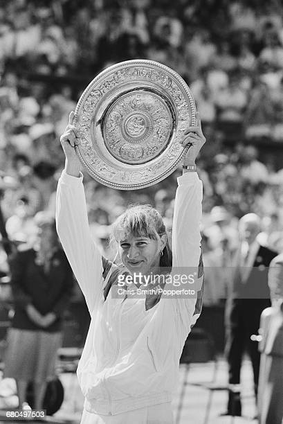 German tennis player Steffi Graf raises the Venus Rosewater Dish trophy in the air in triumph after winning the final of the Ladies' Singles...