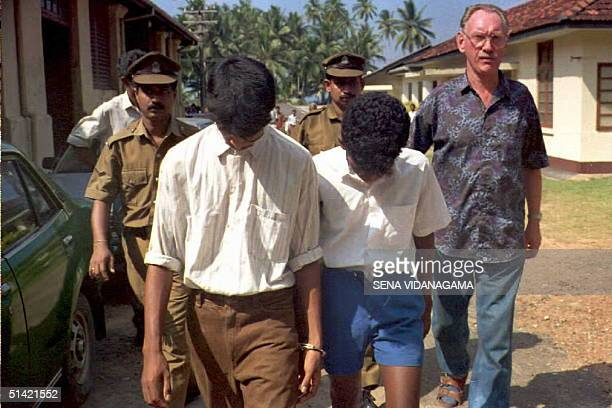 German tourist identified as Guenter Platzdash is escorted out of court in Colombo Sri Lanka 27 January 1995 together with two suspected boy...