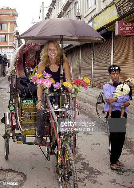 German tourist paddles a rickshaw through a street with its side shops' shutters down at Thamel a tourist area in Kathmandu 29 September 2004 on the...
