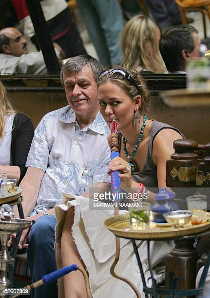 German tourist smokes a shisha at Cairo's famous alFishawi Cafe in the Egyptian capital's old Bazaar 09 April 2005 Many tourists were not deterred by...