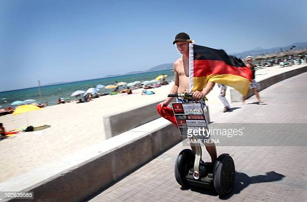 A German tourist waves a German flag while riding a segway at Palma's Beach in Palma de Mallorca on July 6 on the eve of the World Cup semifinal...