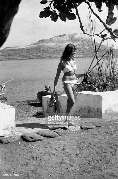 German tourist wearing a bikini and carrying the underwater fishing equipment on the beach of Vulcano Island in the Aeolian archipelago Vulcano 1960s