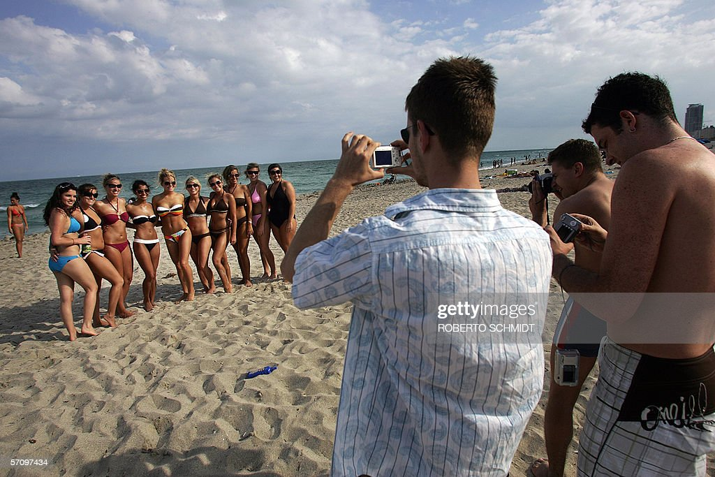 German tourists Jens Seelesch (3rd R) and Robert Pipenhatan (R) take photographs of a group of US college students posing for a photograph in South Beach, Florida 14 March 2006. Thousands of college students come to South Florida from all over the United States to enjoy a spring semester week long break from school this time of the year. AFP PHOTO/ Roberto SCHMIDT