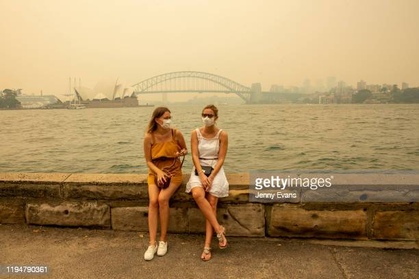 German tourists Julia Wasmiller and Jessica Pryor look on at Mrs Macquarie's chair wearing face masks due to heavy smoke on December 19 2019 in...