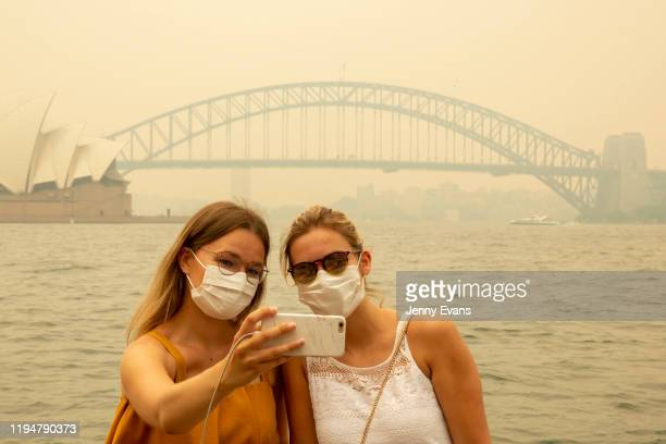 German tourists Julia Wasmiller and Jessica Pryor take a selfie at Mrs Macquarie's chair wearing face masks due to heavy smoke on December 19 2019 in...