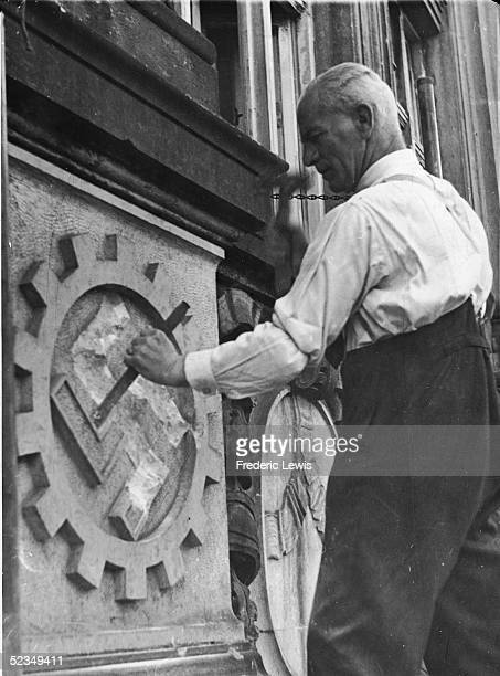 German trade unionist Paul Bebert uses a hammer and chisel to remove a stone swastika from a the facade of an adminstrative building in Hamburg...